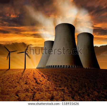 Sunset over the nuclear power plant with wind turbines - stock photo