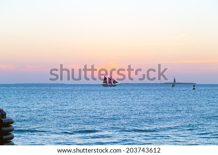 Sunset over the ocean in Key West, Florida. Sailboat under red sail at sunset in rosy clouds.