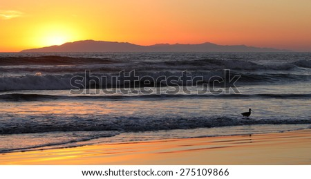 Sunset over the ocean with an island in the background. - stock photo
