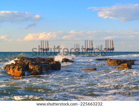 Sunset over the raging sea. Sea station of gas production. Drilling platforms in the sea at sunset against a blue sky - stock photo