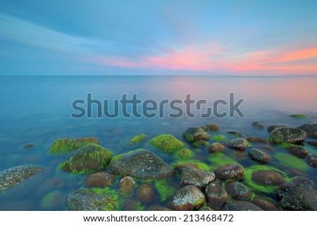 Sunset over the rolling stones of the Norwegian coast, Moelen - stock photo