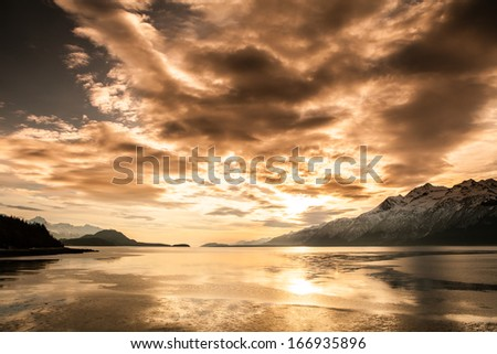 Sunset over the scenic Chilkat Inlet in Southeast Alaska with snow covered mountains in the background. - stock photo