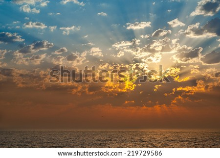 sunset over the sea with dramatic clouds - stock photo
