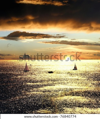 Sunset over the sea with sailing boats - stock photo