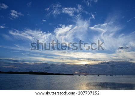 Sunset over the water in the Florida Keys, birds and clouds - stock photo