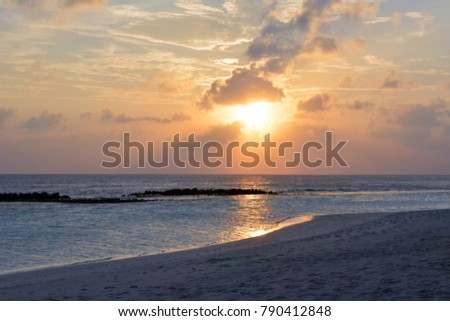 Sunset over the water with cloudy sky in Maldives