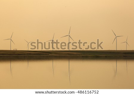 Sunset over the wind farm with reflection on lake