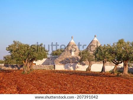 """Sunset over traditional """"Trulli"""" houses of the Apulia region - stock photo"""