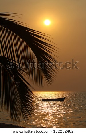 Sunset over water with boat - stock photo