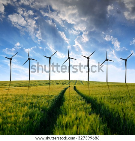 Sunset over wheat fields with wind turbines - stock photo