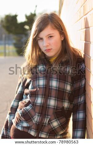 Sunset portrait of a cute teenage girl in schoolyard, leaning on a wall - stock photo