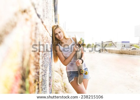 Sunset Portrait of beautiful smiling redhead girl wearing white stands with skateboard based on graffiti wall on sky background with sun set rays light on long hair Empty copy space for inscription - stock photo