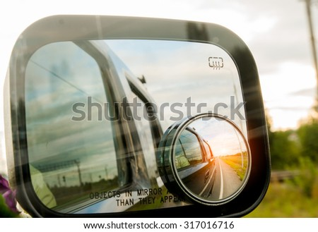 sunset reflected in the mirror of a car - stock photo