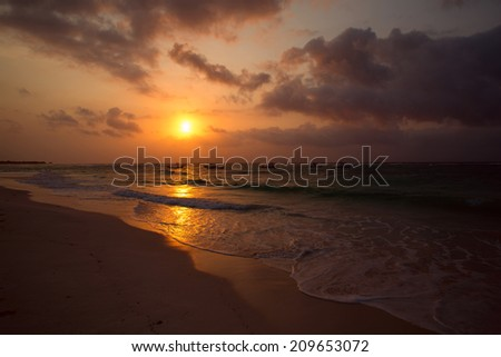 sunset reflecting on the water of the Caribbean sea shore - stock photo