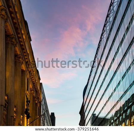 Sunset reflection in glass panels of modern building in Pest part of Budapest city, Hungary, Europe. Old and classical building with columns against new one. Blue sky with red clouds.