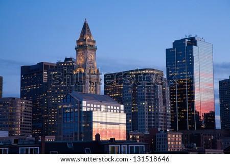 Sunset reflects in windows of Boston skyline and Custom House Tower shot at dusk, Boston, MA - stock photo
