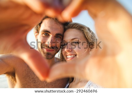 Sunset, sandy beach, a loving couple stops during a walk. A man and a woman are photographed at sunset through a heart made with their hands - stock photo