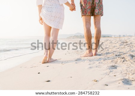 Sunset, sandy beach, a loving couple walks on the deserted beach at sunset during a day at the beach on vacation holding hands. Close up of the shoreline and feet of couple.