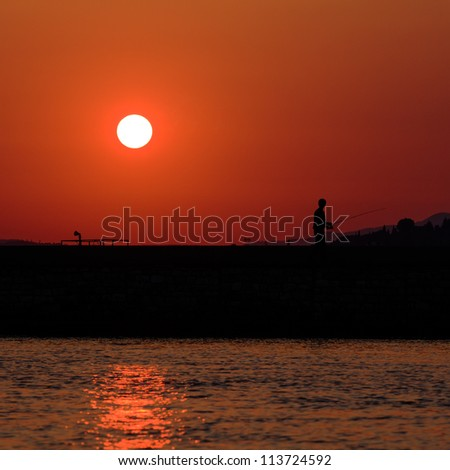 Sunset scene with fisherman - stock photo