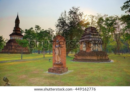 Sunset scenery of the famous Walking Buddha Statue & ruined stupas in Wat Traphang Ngoen, an ancient Buddhist temple in Sukhothai Historical Park, a beautiful UNESCO world heritage site in Thailand - stock photo