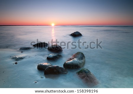 Sunset scenic view over Baltic Sea with stones in foreground. Long exposure.