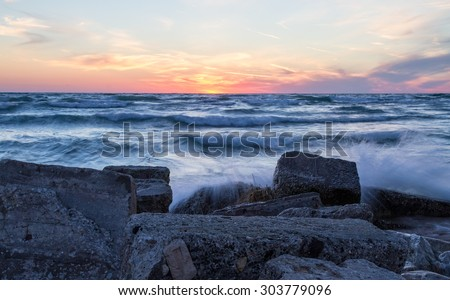 Sunset Shore. Waves crash on a rocky coast as the sun sets over the blue waters of Lake Michigan. Ludington State Park. Ludington, Michigan. - stock photo