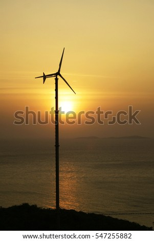 sunset silhouette wind turbine with sea view