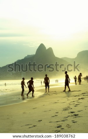 Sunset silhouettes of Brazilians playing keepy uppy beach football altinho on Ipanema Beach Rio de Janeiro Brazil