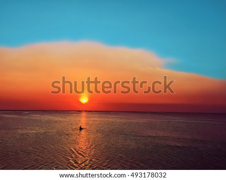 Sunset sky and calm seashore with a boat. Retro digital illustration for card or banner with text place. Yellow sun, vibrant sky, ripples on water surface. Evening ocean landscape in tropical island