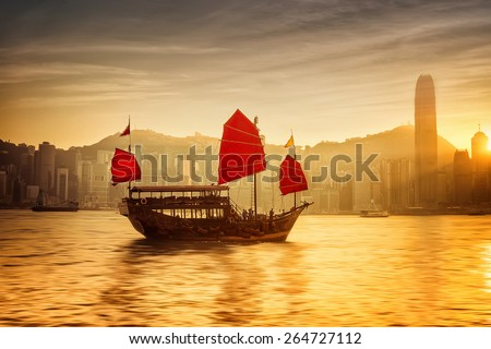 Sunset skyline of Hong Kong with traditional cruise sailboat at Victoria harbor - stock photo