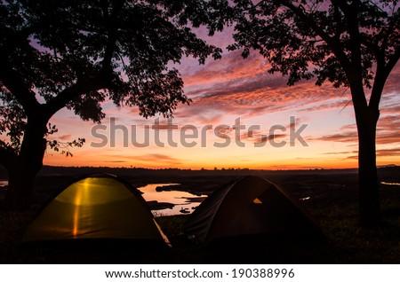 Sunset/sunrise with camping tents at 3000 Boke, Ubon Ratchathani, Thailand - stock photo