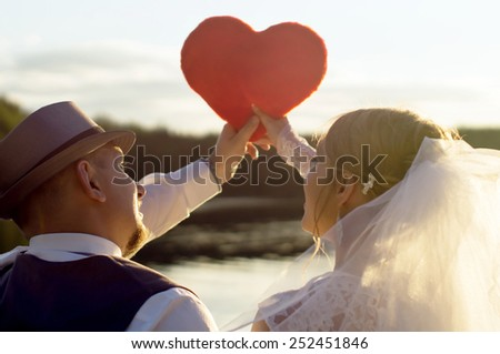 Sunset, the bride and bridegroom holding heart on a background of water - stock photo