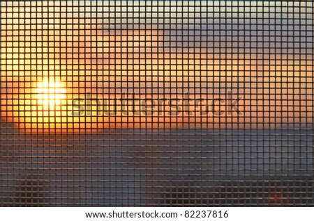 Sunset through the mosquito screen - stock photo
