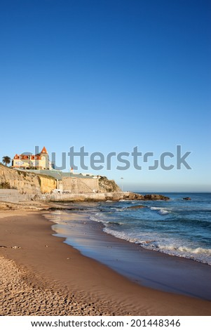 Sunset time at a beach with a cliff on Atlantic Ocean coast in resort town of Estoril in Portugal.