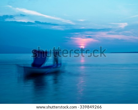 Sunset time on sea, fisherman blur silhouette