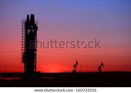 Sunset tower of the pumping unit work in the oil field   - stock photo