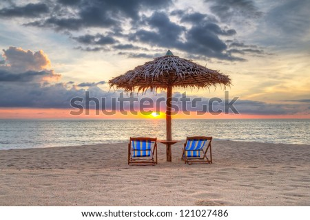 Sunset under parasol on the beach in Thailand - stock photo