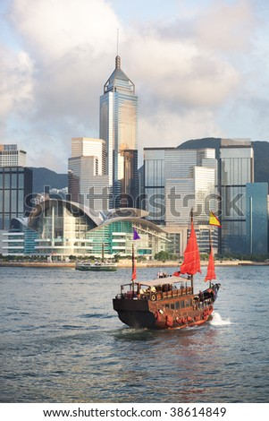 Sunset view of a traditional, junk ship with wind sails shot against modern cityscape of Hong Kong island - stock photo