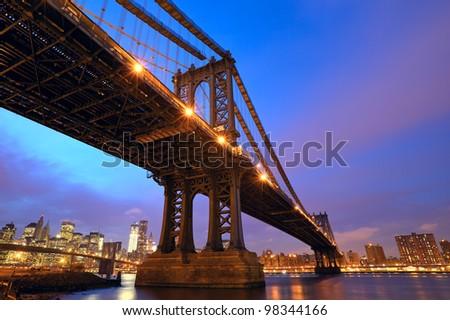 Sunset view of Manhattan Bridge and lower Manhattan skyline with Brooklyn Bridge in New York City - stock photo