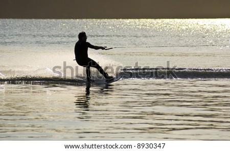 sunset waterskiing wakeboarder sprays water into the air. Afternoon sunlight creates dazzling reflection on lake