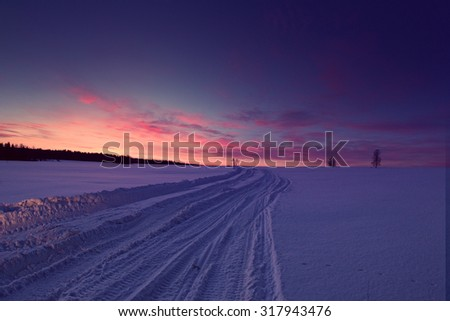 Sunset winter landscape with snow-covered road in violet and pink colors