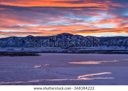 Sunset Winter Mountain Lake - A colorful and bright winter sunset scene of a frozen mountain lake at southwest of Denver-Littleton in Colorado, USA.