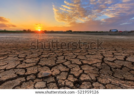 Sunset with a cracked land as foreground
