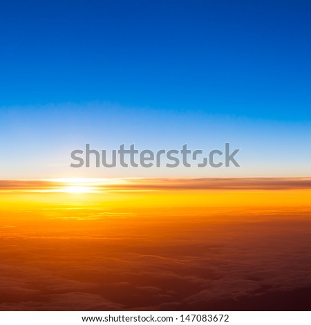 sunset with a height of 10 000 km. Dramatic sunset. View of sunset above clouds from airplane window - stock photo