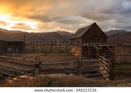 Sunset with an old barn and corral, Heber Valley, Utah, USA. - stock photo