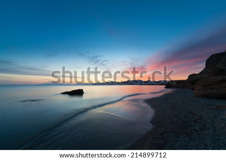 sunset with beautiful clouds reflected in the calm water of the ocean - stock photo