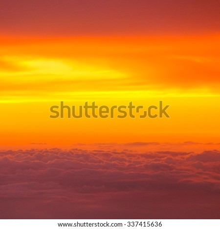Sunset with clouds over view from airplane flying - stock photo