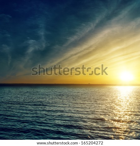 sunset with clouds over water - stock photo