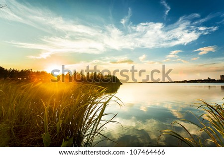 sunset with colorful sky near a urban lake - stock photo