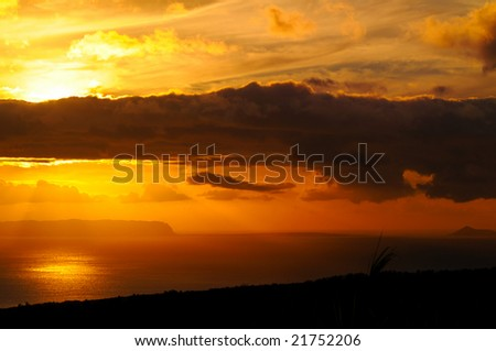 Sunset with dark clouds over the island of Niihau, Hawaii, taken from high ground on Kauai